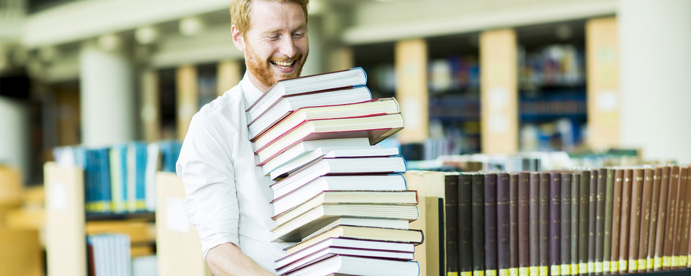 Young man carrying books